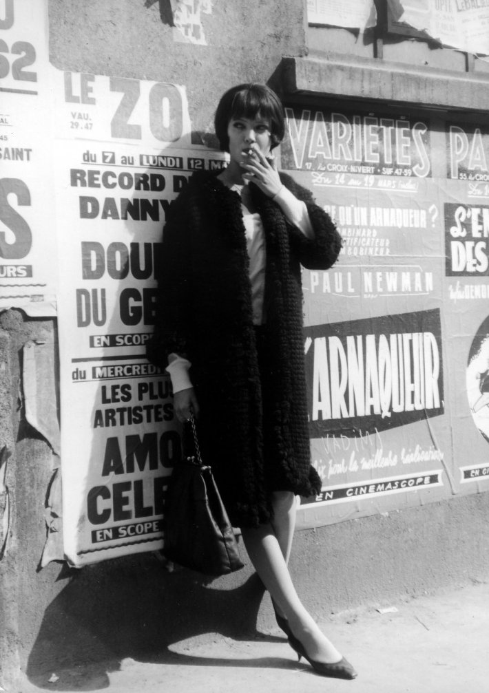 vivre-sa-vie-1962-001-anna-karina-smoking-against-poster-packed-wall-00m-gnt